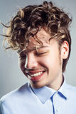 Portrait of young man with curly hairstyle. studio shot. toothy smile and closed eyes.  Stock Image