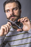 Portrait of a young man cutting his beard with scissors Royalty Free Stock Photography