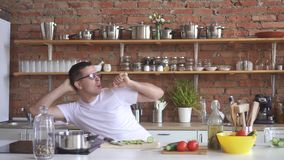 Portrait of a young man dancing and singing in the kitchen, he cuts vegetables stock footage