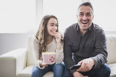 Portrait of a young man and daughter watching TV while eating popcorn on the sofa. A Portrait of a young men and daughter watching TV while eating popcorn on the stock images