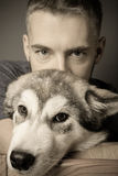 Portrait of a young man with a dog. Toned Stock Image