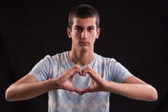 Portrait of young man doing a heart gesture Stock Photo