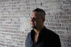 Portrait of a young man, dressed in black shirt. Fashionable hairstyle with shaved temples and slicked back hair at the top of the head, Brick wall, beard, close Royalty Free Stock Photo