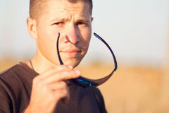 Portrait of a young man dressing sunglasses Stock Photos