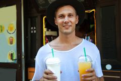 Portrait of young man drink cold drink and milkshake in the streets outdoors. royalty free stock photos