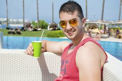Portrait of young man drinking coffee on the beach royalty free stock image