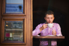 Portrait of a young man drinking coffee and smoking. Stock Image