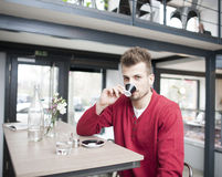 Portrait of young man drinking espresso in cafe Royalty Free Stock Photography