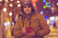 Portrait of young man drinking tea outdoor in wintertime. Over Christmas lights Royalty Free Stock Images