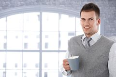 Portrait of young man drinking tea smiling Stock Images