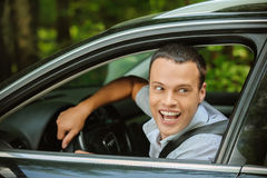 Portrait of young man driving car and greeting somebody with han Stock Images