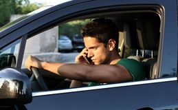 Portrait of young man driving with mobile phone. Portrait of young handsome dark-haired man driving car and speaking on mobile phone Stock Photography