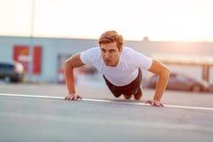 Young man exercising outdoors stock photos