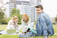 Portrait of young man with female friends studying on university campus Royalty Free Stock Images