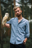 Portrait of young man in forest with owl in hand. Royalty Free Stock Photography
