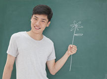 Portrait of young man in front of chalkboard with flower drawing royalty free stock photography