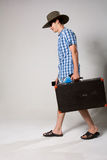 Portrait of a young man in a full-length coming fr. Om the suitcase. On a light background in the studio royalty free stock photography