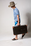 Portrait of a young man in a full-length coming fr. Om the suitcase. On a light background in the studio stock photo