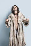 Portrait of young man in fur coat gesturing rock music sign against light blue background Stock Photos