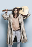 Portrait of young man in fur coat holding guitar against light blue background Stock Photography