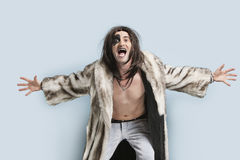 Portrait of young man in fur coat screaming against light blue background Stock Photo