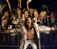 Portrait of young man in fur coat screaming with excited audience in the background Royalty Free Stock Image