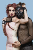 Portrait of young man in gas mask embracing funky woman over blue background Royalty Free Stock Image