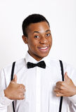 Portrait of young man gesturing thumbs up over white background Stock Images