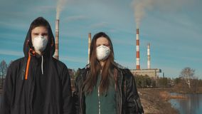 Portrait of a young man and girl in respirators or gas masks. In the background smoke comes from the pipes of a stock video footage