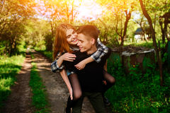 Portrait of young man giving beautiful woman piggyback stock image