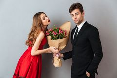 Portrait of a young man giving his girlfriend flower bouquet Royalty Free Stock Photo