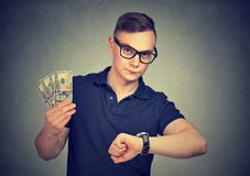 Man holding money checking time. Portrait of a young man in glasses holding money checking time royalty free stock photos