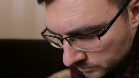 Portrait of a young man with glasses who works with tablet stock video