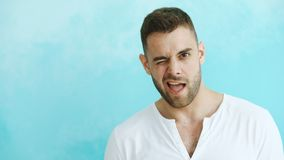 Portrait of young handsome man grimacing into camera and show different emotions on blue background Royalty Free Stock Images