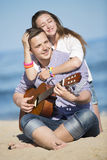 Portrait of young man with guitar and woman on a beach Stock Photography