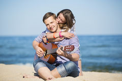 Portrait of young man with guitar and woman on a beach Stock Images