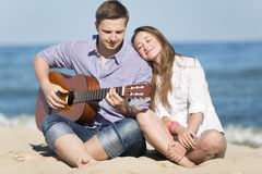 Portrait of young man with guitar and woman on a beach Stock Photo