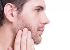 Portrait of young man with hand near the face. Royalty Free Stock Image