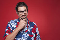 Portrait of a young man in Hawaiian outfit posing with hand on c Royalty Free Stock Photography