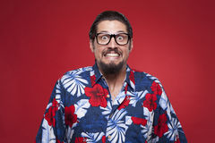 Portrait of a young man in Hawaiian shirt clenching teeth Stock Images