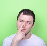 Portrait of a young man with his finger in his nose against gree Stock Photos