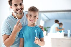 Portrait of young man and his son with toothbrushes in bathroom, space for text. stock photos