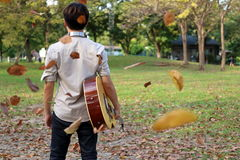 Portrait of young man holding acoustic guitar against among falling leaves in the park.  Royalty Free Stock Photo