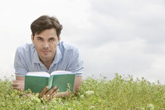 Portrait of young man holding book while lying on grass against sky Stock Photo