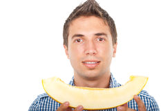 Portrait of young man holding cantaloupe Stock Photo