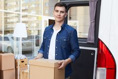 Happy Man Moving House. Portrait of young man holding cardboard box and smiling happily to camera while unloading moving van outdoors stock photos