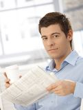 Portrait of young man holding coffee and newspaper Royalty Free Stock Photos