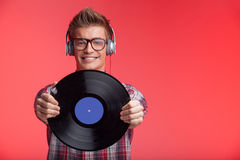Portrait of young man holding disk and wearing headphones. Royalty Free Stock Images