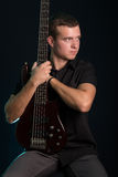 Portrait of young man holding electric bass guitar Stock Image