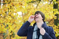 Portrait of a young man holding hat laughing outdoors. Close up portrait of a young man holding hat laughing outdoors royalty free stock images